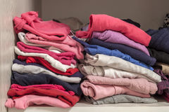 A stack of knitted warm woolen clothes in wardrobe close up Royalty Free Stock Image