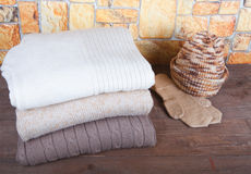 Stack of knitting clothes, hat and mittens on wooden table oppos Stock Photo