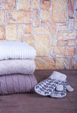 Stack of knitting clothes and painted mittens on wooden table op Stock Photo
