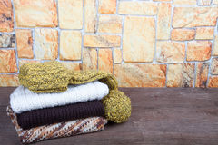 Stack of knitting clothes on wooden table opposite a stony wall Stock Photography