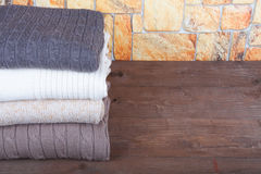 Stack of knitting clothes on wooden table opposite a stony wall Royalty Free Stock Photos