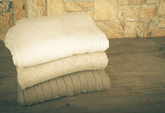 Stack of knitting clothes on wooden table opposite a stony wall. Royalty Free Stock Photos