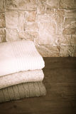 Stack of knitting clothes on wooden table opposite a stony wall. Stock Photos