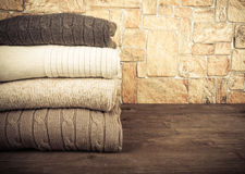 Stack of knitting clothes on wooden table opposite a stony wall. Royalty Free Stock Image