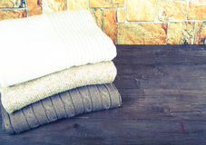 Stack of knitting clothes on wooden table opposite a stony wall. Royalty Free Stock Photography