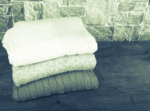 Stack of knitting clothes on wooden table opposite a stony wall. Stock Images