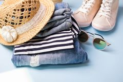 Stack of ladies summer clothes  and accessories.  Jeans overalls, glasses, sneakers, wicker hat, striped top. Casual clothes for travel royalty free stock photo