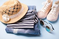 Stack of ladies summer clothes  and accessories.  Jeans overalls, glasses, sneakers, wicker hat, striped top.  Casual clothes. For travel stock photography