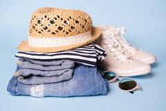 Stack of ladies summer clothes  and accessories.  Jeans overalls, glasses, sneakers, wicker hat, striped top.  Casual clothes. For travel stock image