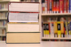 Stack of large books and a library shelf Stock Photos