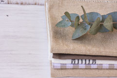 Stack of linen and cotton kitchen towels with branch of silver dollar eucalyptus on white wood table Royalty Free Stock Images