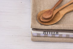Stack of linen cotton kitchen towels, handmade wooden spoons, on white kitchen table, Provence style Stock Images