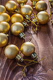 Stack of little christmas gold baubles on wooden board Royalty Free Stock Photography