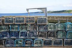 Stack of lobster net pots at harbour by stone wall for fisherman to catch sea fish and food. Uk stock photo