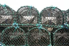Stack of lobster traps or lobster cages. On quay Stock Photo