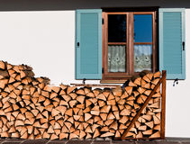 Stack of logs in front of the window Royalty Free Stock Photo