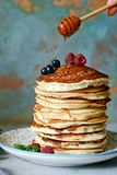 A stack of lush punkcakes for breakfast on a gray background. High pile of delicious pancakes with berries. Stock Photos