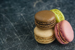 Stack of macaroons on a scratched old chalkboard background. Space for text royalty free stock images