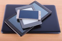 Stack made of different gadgets: from smartphone, ebook reader,. Tablet device and a notebook on a wooden table Royalty Free Stock Image