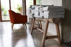 Stack of magazine books on wooden table shelf in living room Stock Image