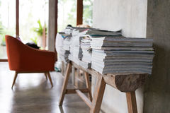 Stack of magazine books on wooden table shelf in living room Royalty Free Stock Photos