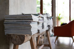 Stack of magazine books on wooden table shelf in living room Stock Photos