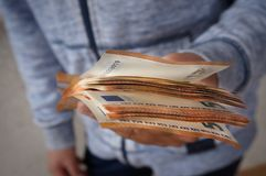 Stack of money in hand. Person holding a pack of fifty euros banknotes in hands stock photos
