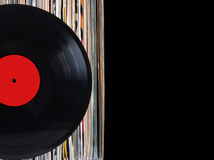 Stack of many vinyl records in old color covers on left side on photo on black background Stock Image
