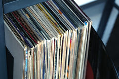 Stack of many vinyl records in old color covers on a shelf side view Royalty Free Stock Photos
