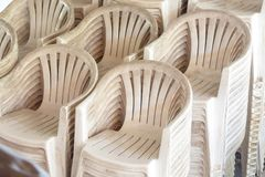 Stack of Many White and Old Plastic Chairs Outdoor stock images