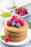 Stack of matcha pancakes served blueberry and raspberry on white plate, vertical