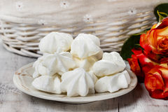 Stack of meringues. Red roses in the background Royalty Free Stock Photography