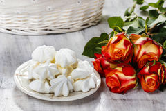 Stack of meringues. Red roses in the background Stock Photography