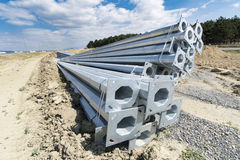 Stack of metal pipes. At manufacturing plant construction site. Road construction light posts Stock Photos