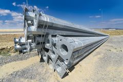 Stack of metal pipes at manufacturing plant construction site. Road construction light posts Royalty Free Stock Images