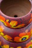Stack of Mexican ceramic pots, purple background, orange flowers Stock Photo
