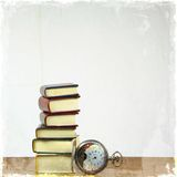 Stack of miniature books and old pocket watch. Stock Image
