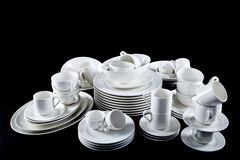 Mixed white dishes cups and plates isolated on black Stock Images