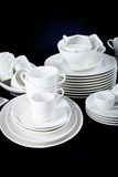 Mixed white dishes cups and plates isolated on black Stock Photo