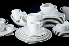 Mixed white dishes cups and plates isolated on black Royalty Free Stock Photos