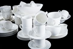 Mixed white dishes cups and plates isolated on black Stock Photography