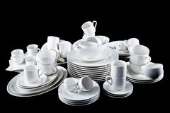 Mixed white dishes cups and plates isolated on black Stock Photos
