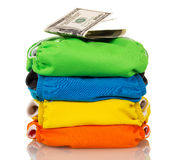 Stack modern cloth diapers and dollars isolated on white background. Royalty Free Stock Images