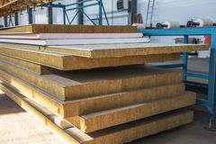 Stack of modern sandwich panel blocks from metal profile and wool foam for building warm and sound protected houses.  royalty free stock photography