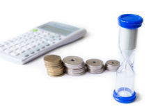 Stack of money with calculator and hourglass isolated white back Stock Image