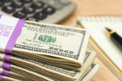 Stack of Money, Calculator, Paper and Pen. Stack of Money, Calculator, Pad of Paper and Pen with Narrow Depth of Field Royalty Free Stock Photos