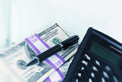 Stack of money with a calculator a pen and a general ledger Royalty Free Stock Photo
