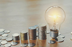 Stack money coins  growing light bulb concept Stock Photography