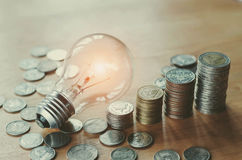 Stack money coins with growing light bulb Stock Photo