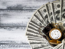 Stack of money dollars laid out like a fan with antique gold watch Stock Images